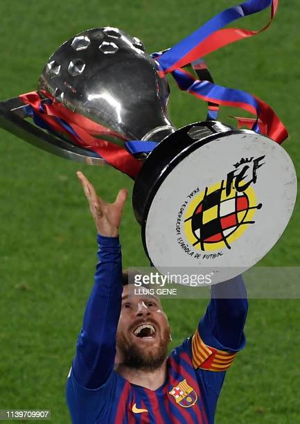 Barcelona's Argentinian forward Lionel Messi tosses La Liga trophy as he celebrates becoming La Liga champions after winning the Spanish League...