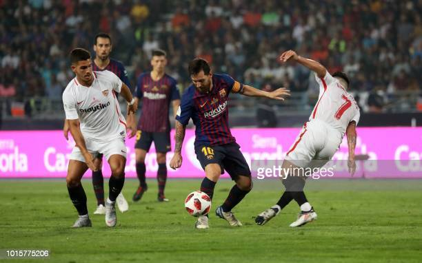 Barcelona's Argentinian forward Lionel Messi vies for the ball with Sevilla's Spanish midfielder Roque Mesa and Sevilla's Portuguese forward Andre...