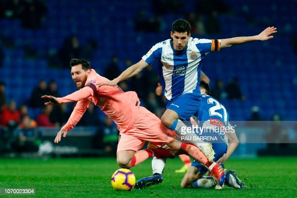 Barcelona's Argentinian forward Lionel Messi vies for the ball with Espanyol's Spanish midfielder Marc Roca and Espanyol's Spanish defender Javier...