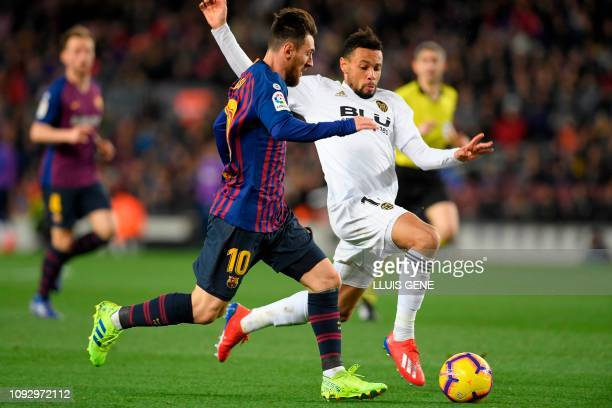 Barcelona's Argentinian forward Lionel Messi vies for the ball with Valencia's French midfielder Francis Coquelin during the Spanish league football...