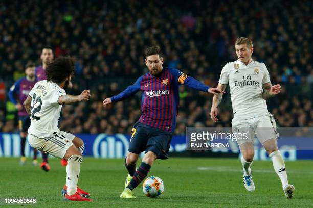 TOPSHOT Barcelona's Argentinian forward Lionel Messi vies for the ball with Real Madrid's Brazilian defender Marcelo and Real Madrid's German...