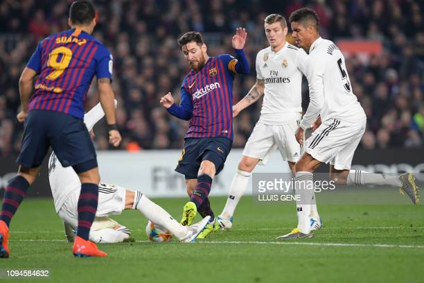 Barcelona's Argentinian forward Lionel Messi vies for the ball with Real Madrid's German midfielder Toni Kroos and Real Madrid's French defender...