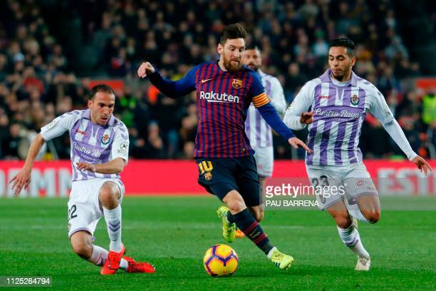 Barcelona's Argentinian forward Lionel Messi vies for the ball with Real Valladolid's Spanish defender Nacho and Real Valladolid's Spanish midfielder...