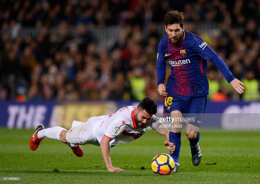 Barcelona's Argentinian forward Lionel Messi (R) vies with Alaves' Spanish defender Ruben Duarte during the Spanish league football match between FC Barcelona and Deportivo Alaves at the Camp Nou stadium in Barcelona on January 28, 2018. / AFP PHOTO / Josep LAGO