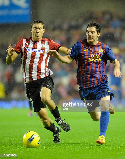 FC Barcelona's Argentinian forward Lionel Messi vies with Athletic Bilbao's forward Oscar de Marcos during their Spanish football match Athletic...
