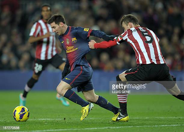 Barcelona's Argentinian forward Lionel Messi vies with Athletic Bilbao's defender Fernando Amorebieta during the Spanish league football match FC...