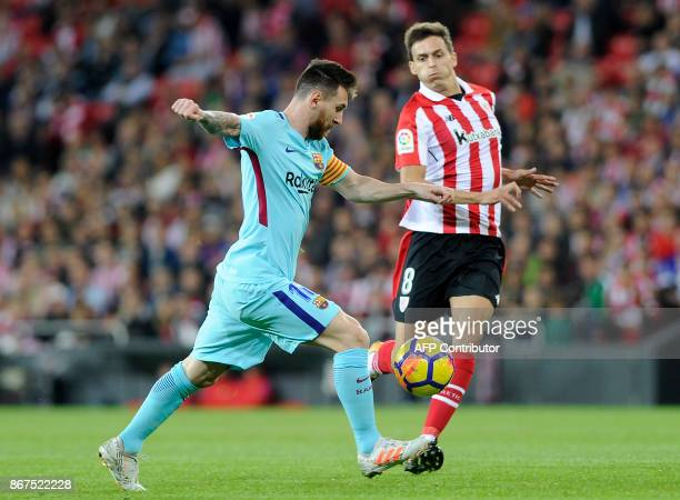 Barcelona's Argentinian forward Lionel Messi vies with Athletic Bilbao's Spanish midfielder Ander Iturraspe during the Spanish league football match...