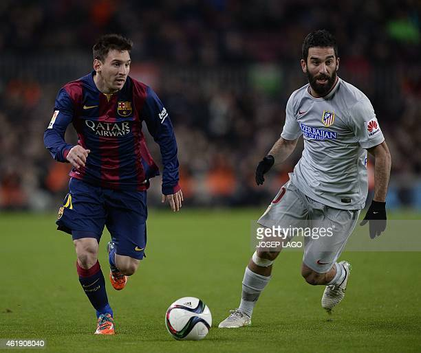 Barcelona's Argentinian forward Lionel Messi vies with Atletico Madrid's Turkish midfielder Arda Turan during the Spanish Copa del Rey quarter final...