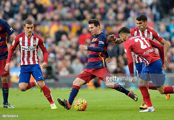 Barcelona's Argentinian forward Lionel Messi vies with Atletico Madrid's French forward Antoine Griezmann and Atletico Madrid's Argentinian...