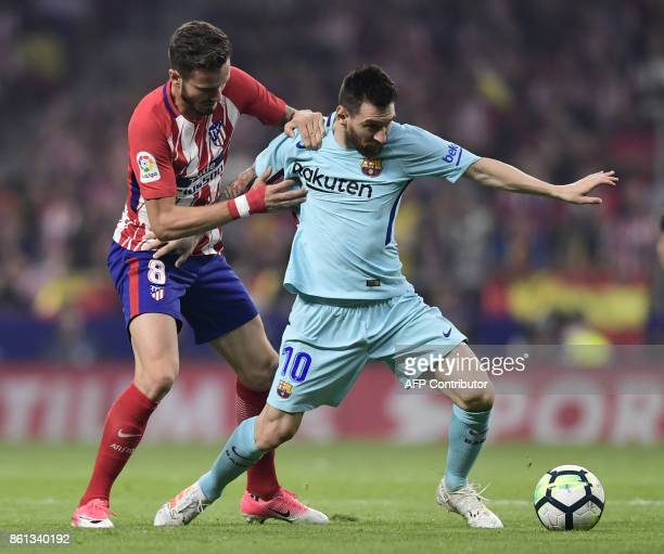 Barcelona's Argentinian forward Lionel Messi vies with Atletico Madrid's Spanish midfielder Saul Niguez during the Spanish league football match Club...