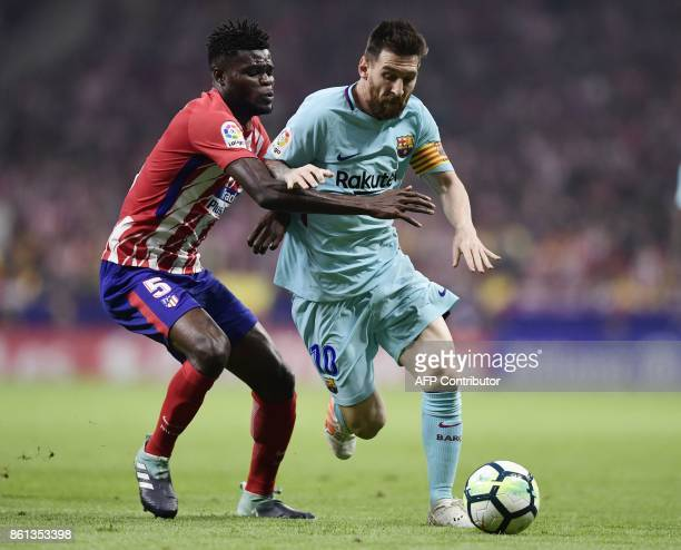 Barcelona's Argentinian forward Lionel Messi vies with Atletico Madrid's Ghanaian midfielder Thomas during the Spanish league football match Club...