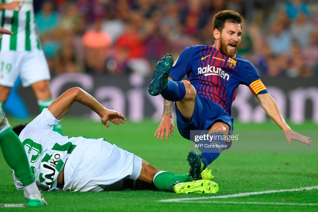 TOPSHOT - Barcelona's Argentinian forward Lionel Messi (R) vies with Betis' Algerian defender Aissa Mandi during the Spanish league footbal match FC Barcelona vs Real Betis at the Camp Nou stadium in Barcelona on August 20, 2017. /