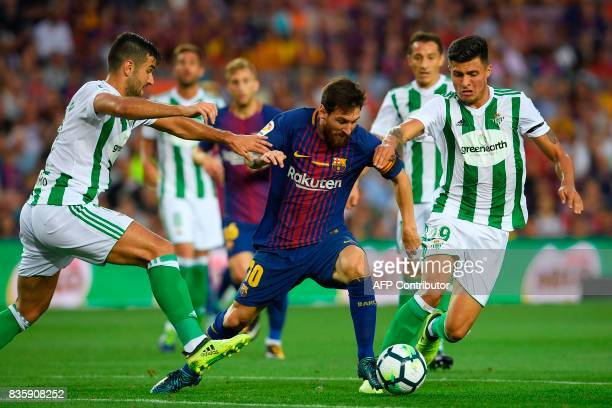 Barcelona's Argentinian forward Lionel Messi vies with Betis' forward Alex Alegria and Betis's Colombian forward Juan Narvaez during the Spanish...