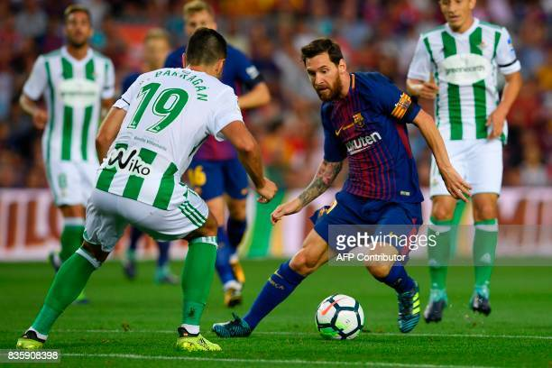 Barcelona's Argentinian forward Lionel Messi vies with Betis' forward Alex Alegria during the Spanish league footbal match FC Barcelona vs Real Betis...