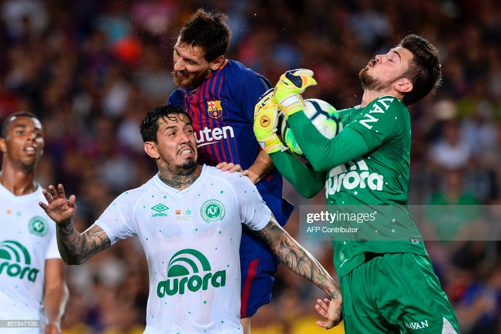 Barcelona's Argentinian forward Lionel Messi (C) vies with Chapecoense's goalkeeper Elias Martello (R) and Chapecoense's defender Victor Ramos during the 52nd Joan Gamper Trophy friendly football match between Barcelona FC and Chapecoense at the Camp Nou stadium in Barcelona on August 7, 2017. Funds raised from the match will 'help Chapecoense rebuild institutionally and recover the competitive level it had before the tragedy', Barca said in a statement as the Brazilian side still reeling from a devastating plane crash that killed 19 players and 24 club officials last year. / AFP PHOTO / Josep LAGO