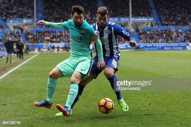 Barcelona's Argentinian forward Lionel Messi vies with Deportivo Alaves defender Victor Laguardia during the Spanish league football match Deportivo...