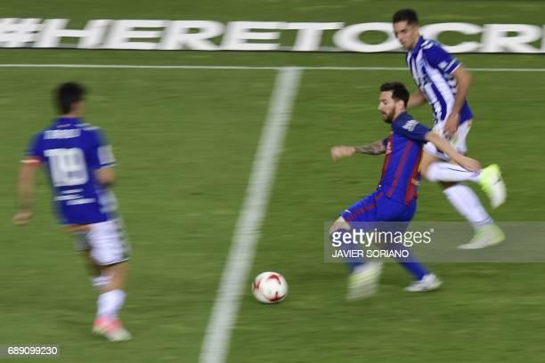 Barcelona's Argentinian forward Lionel Messi vies with Deportivo Alaves' forward Ruben Sobrino and Deportivo Alaves' midfielder Manu Garcia during...