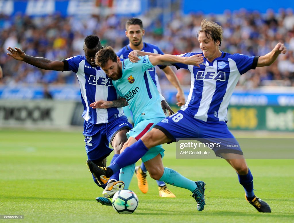 Barcelona's Argentinian forward Lionel Messi (C) vies with Deportivo Alaves' Ghanaian forward Wakaso Mubarak (L) and midfielder Tomas Pina (R) during the Spanish league football match Deportivo Alaves vs FC Barcelona at the Mendizorroza stadium in Vitoria on August 26, 2017. /