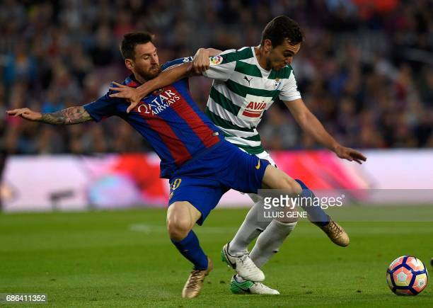 Barcelona's Argentinian forward Lionel Messi vies with Eibar's midfielder Gonzalo Escalante during the Spanish league football match FC Barcelona vs...