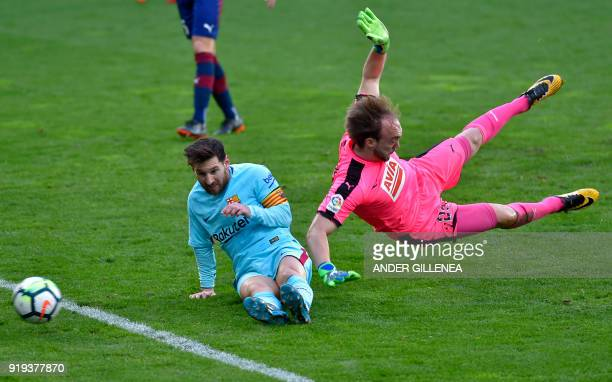 Barcelona's Argentinian forward Lionel Messi vies with Eibar's Serbian goalkeeper Marko Dmitrovic during the Spanish league football match between SD...