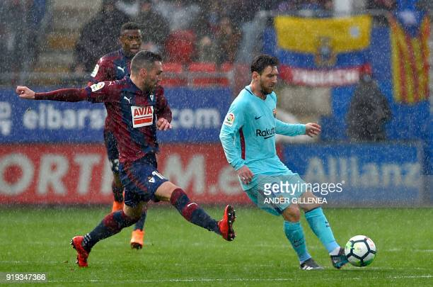 TOPSHOT Barcelona's Argentinian forward Lionel Messi vies with Eibar's Spanish defender Anaitz Arbilla during the Spanish league football match...