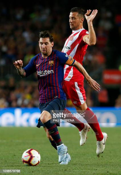 Barcelona's Argentinian forward Lionel Messi vies with Girona's Spanish midfielder Alex Granell during the Spanish league football match between FC...