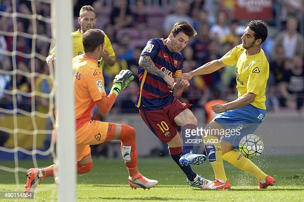 Barcelona's Argentinian forward Lionel Messi vies with Las Palmas' goalkeeper Javi Varas and Las Palmas' defender Pedro Bigas Rigo prior to getting...
