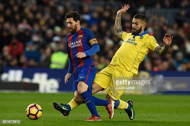 Barcelona's Argentinian forward Lionel Messi vies with Las Palmas' Croatian forward Marko Livaja during the Spanish league football match FC...