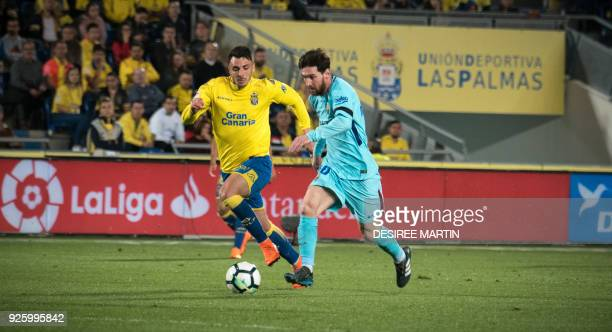 Barcelona's Argentinian forward Lionel Messi vies with Las Palmas' defender Ximo Navarro Jimenez during the Spanish league football match UD Las...