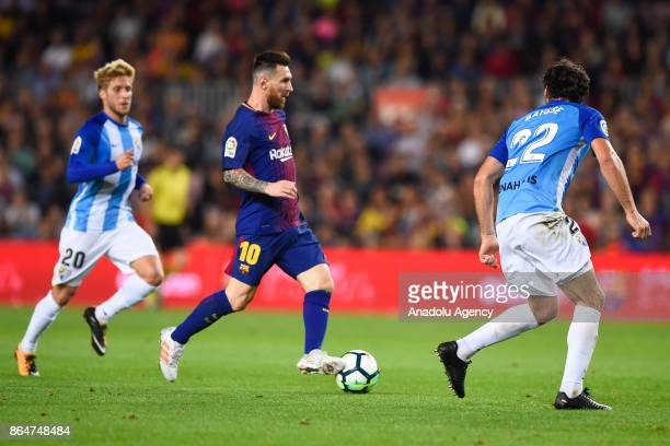 Barcelona's Argentinian forward Lionel Messi vies with Malaga's midfielder Sergio Gontan during the Spanish league football match FC Barcelona vs...
