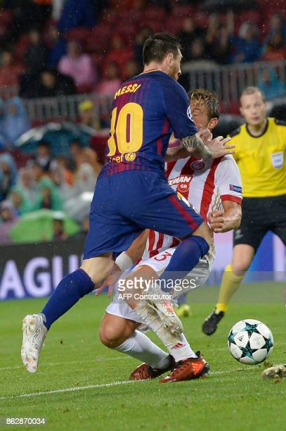 Barcelona's Argentinian forward Lionel Messi vies with Olympiacos' Spanish defender Alberto Botia during the UEFA Champions League group D football...