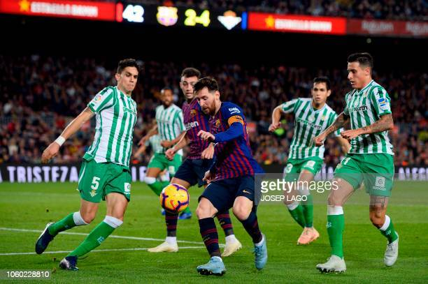 TOPSHOT Barcelona's Argentinian forward Lionel Messi vies with Real Betis' Spanish defender Marc Bartra during the Spanish league football match...