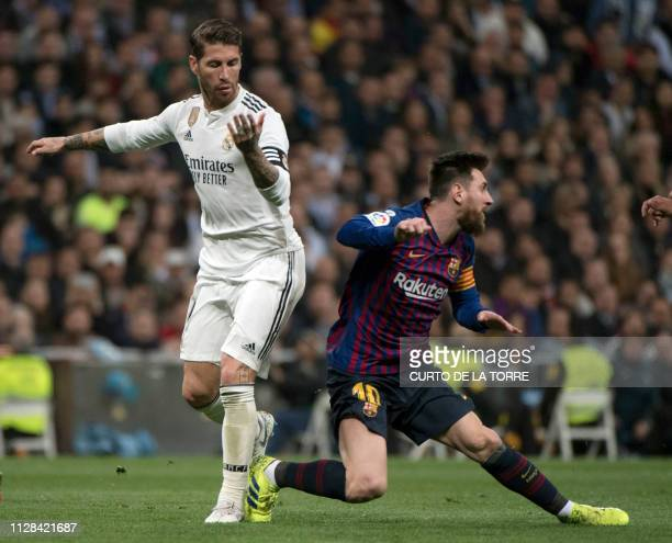Barcelona's Argentinian forward Lionel Messi vies with Real Madrid's Spanish defender Sergio Ramos during the Spanish league football match between...