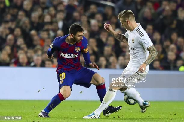 Barcelona's Argentinian forward Lionel Messi vies with Real Madrid's German midfielder Toni Kross during Spanish El Clasico football match between FC...