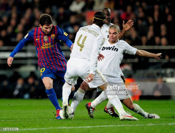Barcelona's Argentinian forward Lionel Messi vies with Real Madrid's defender Sergio Ramos and Real Madrid's Portuguese defender Pepe during the...