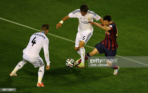 Barcelona's Argentinian forward Lionel Messi vies with Real Madrid's defender Sergio Ramos and Real Madrid's Portuguese defender Fabio Coentrao...