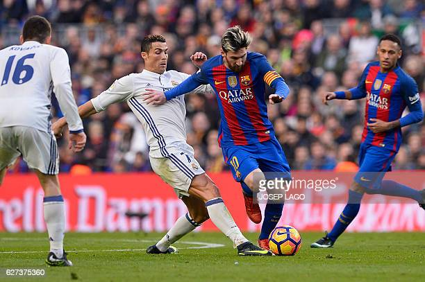 Barcelona's Argentinian forward Lionel Messi vies with Real Madrid's Portuguese forward Cristiano Ronaldo during the Spanish league football match FC...