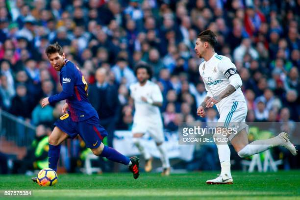 Barcelona's Argentinian forward Lionel Messi vies with Real Madrid's Spanish defender Sergio Ramos during the Spanish League 'Clasico' football match...