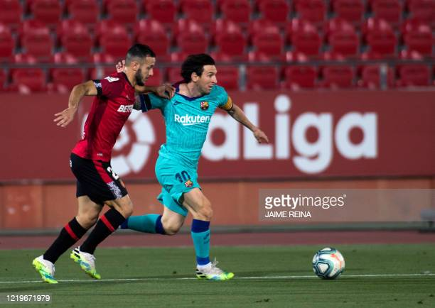 Barcelona's Argentinian forward Lionel Messi vies with Real Mallorca's Spanish defender Joan Sastre during the Spanish League football match between...