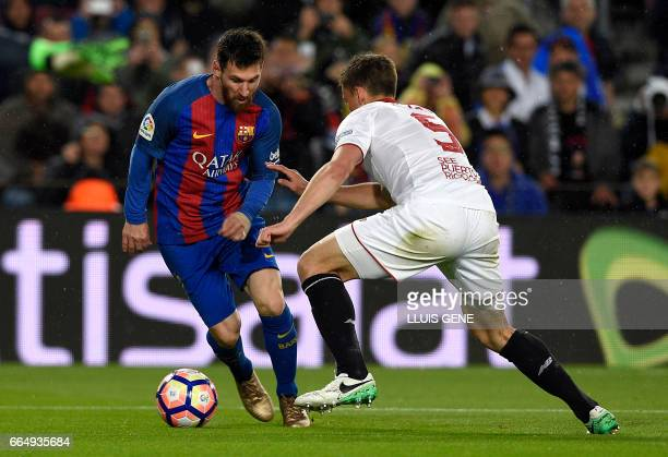 Barcelona's Argentinian forward Lionel Messi vies with Sevilla's French defender Clement Lenglet during the Spanish league football match FC...