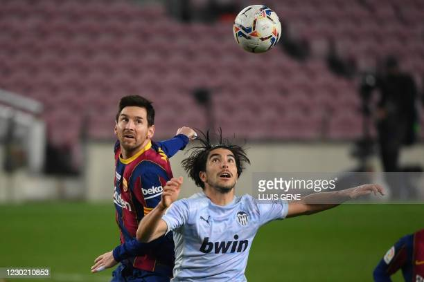 Barcelona's Argentinian forward Lionel Messi vies with Valencia's Spanish midfielder Carlos Soler during the Spanish league football match between FC...