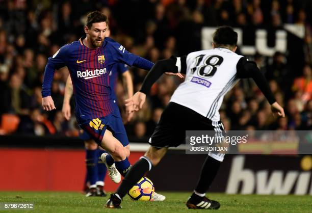 Barcelona's Argentinian forward Lionel Messi vies with Valencia's midfielder Carlos Soler during the Spanish league football match Valencia CF and FC...