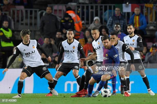 Barcelona's Argentinian forward Lionel Messi vies with Valencia's defense during the Spanish 'Copa del Rey' first leg semifinal football match...
