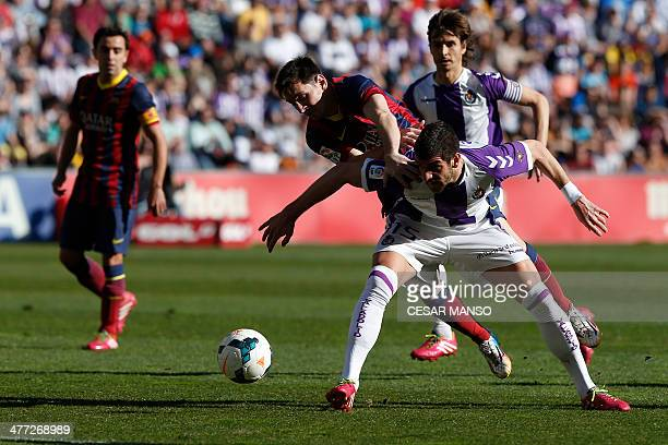 Barcelona's Argentinian forward Lionel Messi vies with Valladolid's Serbian defender Stefan Mitrovic during the Spanish league football match Real...
