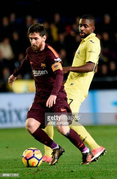 Barcelona's Argentinian forward Lionel Messi vies with Villarreal's Congolese forward Cedric Bakambu during the Spanish league football match between...