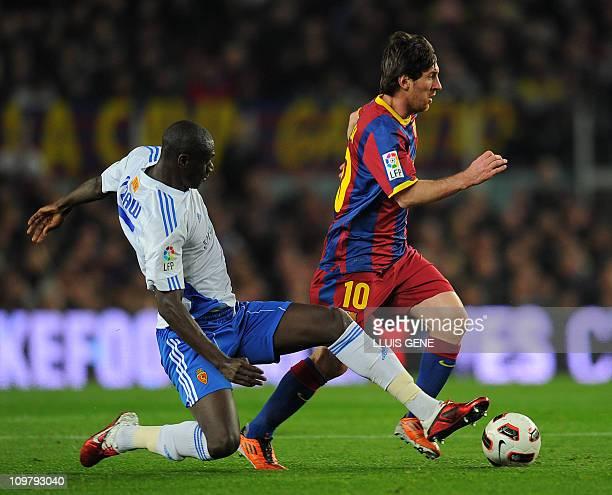 Barcelona's Argentinian forward Lionel Messi vies with Zaragoza's midfielder Guirane N'Daw during the UEFA Spanish League football match FC Barcelona...