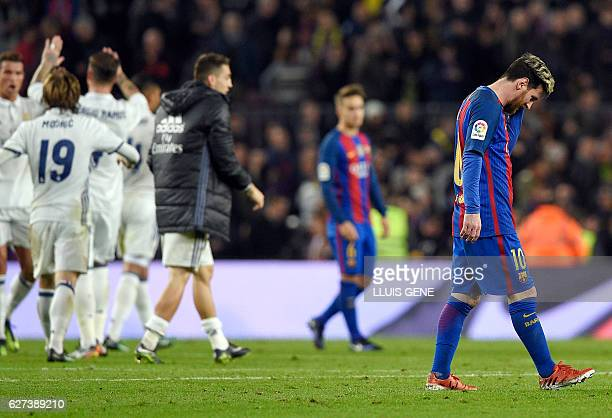 Barcelona's Argentinian forward Lionel Messi walks on the pitch as Real Madrid players celebrate during the Spanish league football match FC...