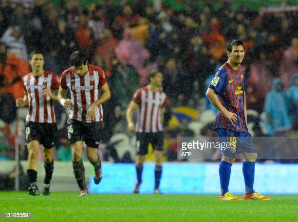 FC Barcelona's Argentinian forward Lionel Messi walks past Athletic Bilbao's players celebrating their goal after scoring his team's first goal...