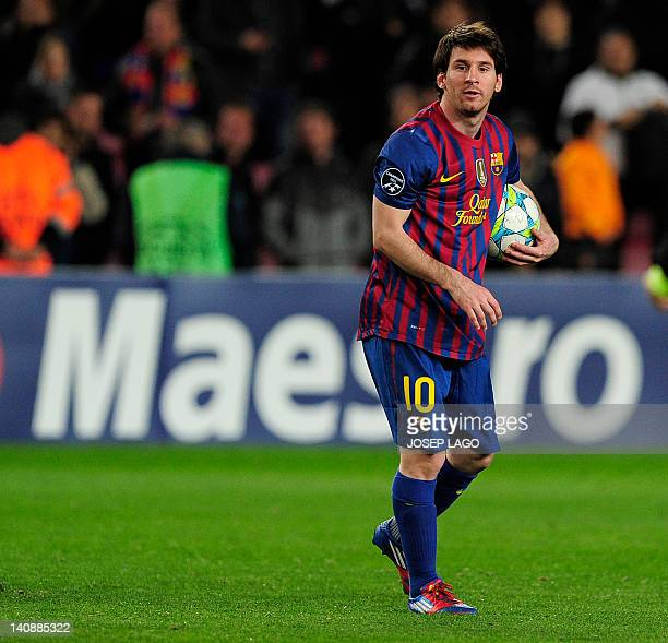 Barcelona's Argentinian forward Lionel Messi walks with the ball after he scored five goals during the Champions League round of sixteen second leg...
