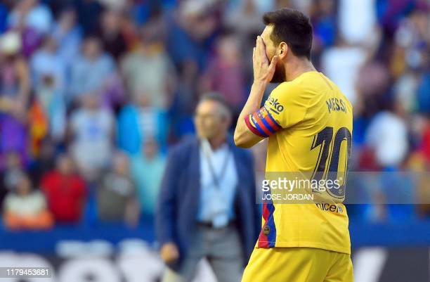 Barcelona's Argentinian Forward Lionel Messi wipes his face at the end of the Spanish League football match between Levante UD and FC Barcelona at...